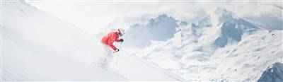 Skier on a downhill run in the mountains